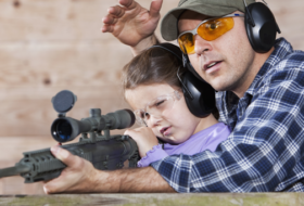 Father teaches daughter to shoot a gun