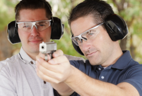 Man firing a gun with an instructor watching